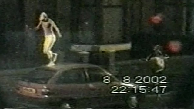 Youths jumping on a car