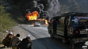 Pakistani onlookers watch a burning Nato oil tanker in Khyber tribal district