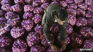 A worker packs onions in India