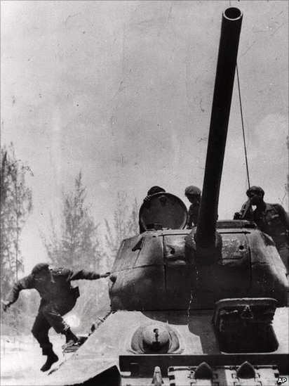 Fidel Castro jumps from a tank as he arrives at Giron, Cuba, near the Bay Of Pigs