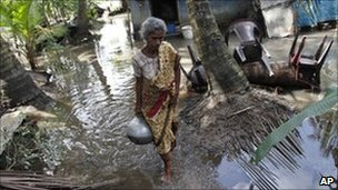 A woman carries a pot of drinking water at her flooded house in Kartivu, east of Colombo