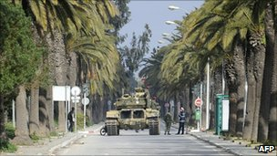 Soldiers stand guard near a tank on a street of Tunis on January 16, 2011.