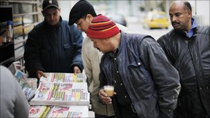 Men look at newspapers at a street kiosk in downtown Tunis