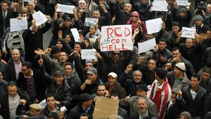 """Tunisian protesters hold placards reading """"RCD go to hell"""" in Tunis, 18 January"""
