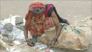 Woman looking through rubbish to see if anything can be salvaged - photo James Melik