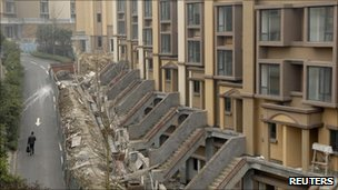 A man walks past buildings under construction at a residential complex in Chongqing municipality