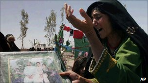 An Afghan woman mourns as she holds a poster with photos of her family members killed during a US-led raid in Herat province in Afghanistan in 2008