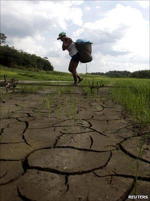 Man carring basket across dry ground