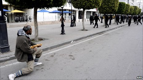 A Tunisian demonstrator holds his bread stick like a weapon in front of riot police during a protest in Tunis on 18 January 2011