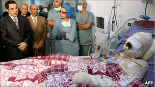 Tunisia's then leader (l) visiting Mohamed Bouazizi on 28 December 2010
