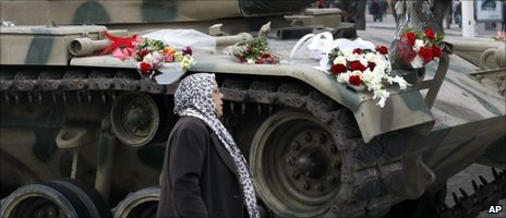 A woman walks past a tank as flowers are displayed on it in the centre of Tunis, 18 January 2011