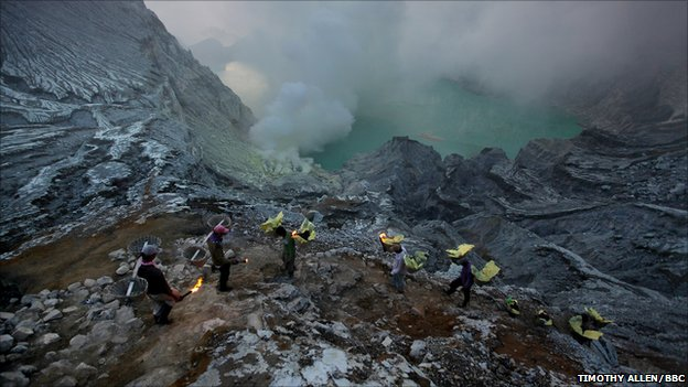 A procession of miners in the crater of Ijen volcano in East Java, Indonesia