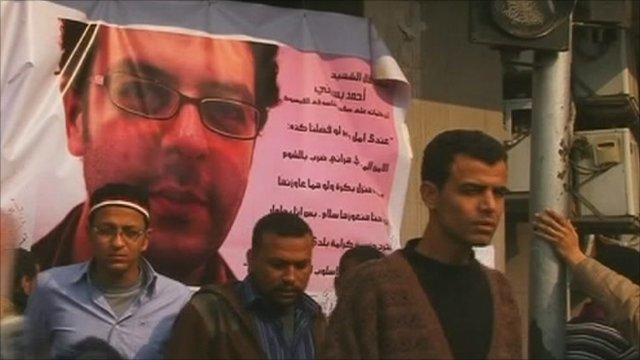 Protesters by a makeshift shrine of Ahmed Basiony, who was killed in Tahrir Square