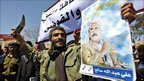 A supporter of the Yemeni government holds a poster of President Ali Abdullah Saleh and waves a dagger in Sanaa, 14 February 2011