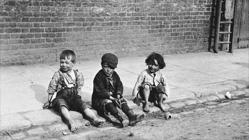 Street photography in london three young children sit on the pavement next to the curb 1892 photo