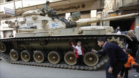 A man photographs his daughter on an Egyptian army tank, in Tahrir Square - 14 February 2011