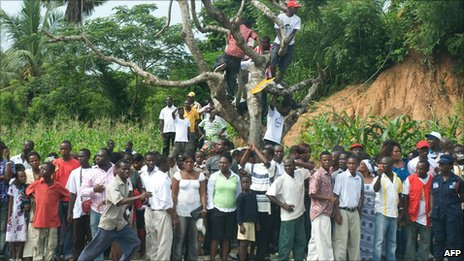 Ghanaians on the side of the road waiting to see a motorcade (2009)