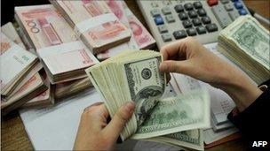 A bank teller counting stacks of US dollars and Chinese Yuan notes