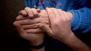 Carer holds elderly patient's hand
