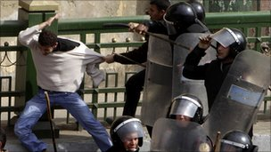Police beat a protester during clashes in Cairo on 28 January, 2011