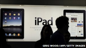 People in front of an iPad advert