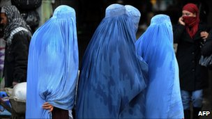 Afghan women wearing burqas walk past shops at a market in Kabul on February 13, 2011