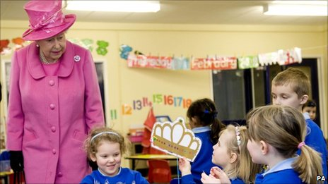 The Queen dressed in pink is shown a picture of a crown by a schoolgirl