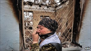 An ethnic Uzbek woman cries as she passes a burned-out house in Osh, Southern Kyrgyzstan in June 2010