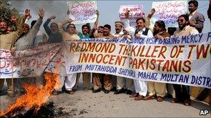Pakistani protesters burn a US flag