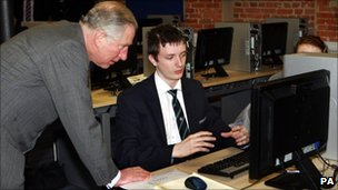 Prince Charles talks to Kristofer Anstey, 14, who was working on pump designs for a Rolls Royce engine during a visit to the JCB Academy.