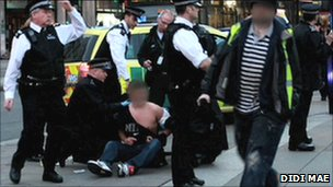 Police holding a man in Trafalgar Square following the brawl