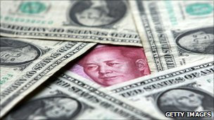 Face of Mao Zedong peaks out from a yuan note concealed in amongst dollar bills