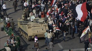 Demonstrators walk by an army vehicle in Tahrir Square on 18 February.