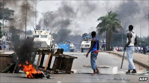 UN peacekeepers drive past supporters of Alassane Ouattara as they demonstrate in Abidjan on 19 February 2011