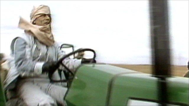 Muammar Gaddafi riding a tractor