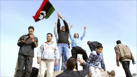 Residents stand on a tank holding a pre-Gaddafi era national flag inside a security forces compound in Benghazi, Libya on Monday, Feb. 21, 2011
