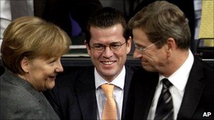 German Chancellor Angela Merkel, Defence Minister Karl-Theodor zu Guttenberg and Foreign Minister Guido Westerwelle, talk prior to a debate at the Bundestag in Berlin, Germany, 21 January 2011