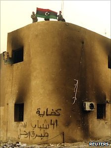 Libyan protesters display the country's pre-Gaddafi flag on top of a building during a demonstration in the seaport city of Tobruk, 20 February 2011