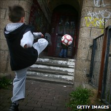 Boy kicking football in street - generic