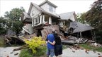 Murray and Kelly James look at their damaged house in central Christchurch, New Zealand, 23 February 2011