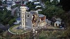 The wrecked Timeball Station, a Victorian building that historically indicated the time to ships sailing by its ball on top of the stone tower, stands on a hill above the town of Lyttelton, 23 February 2011