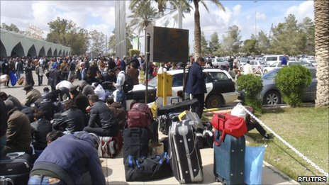 People waiting to be evacuated from Libya gather outside Tripoli airport