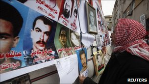 A man looks at photographs of people killed during the uprising in Benghazi (23 February 2011)