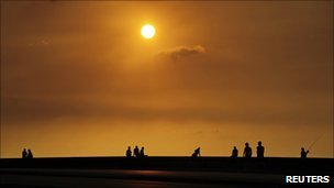 People sit along Havana's seafront boulevard, El Malecon, during sunset
