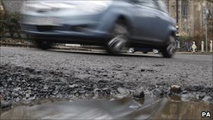 A car passes a pothole (Photo: Danny Lawson/PA Wire)