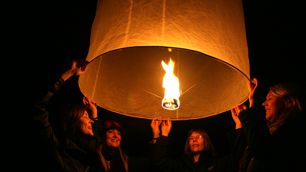 People releasing a Chinese lantern