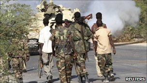 Somali government soldiers patrol along a main road in Warshadaha, 23 February 2011 during clashes between Islamist insurgents and government troops in the capital Mogadishu