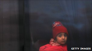 A girl who recently fled Libya sits on a bus with other displaced persons on the Tunisian side of the border on 23 February 2011 in Jdir, Tunisia