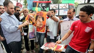 Libyan protesters burn pictures of Libyan leader Muammar Gaddafi during a demonstration in Kuala Lumpur on 25 February 2011.