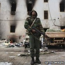 An opposition militiaman stands guard in front of the charred national security building on 24 February 2011 in Benghazi, Libya